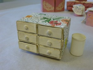 Handmade dolls house white and floral patterned match box drawers.